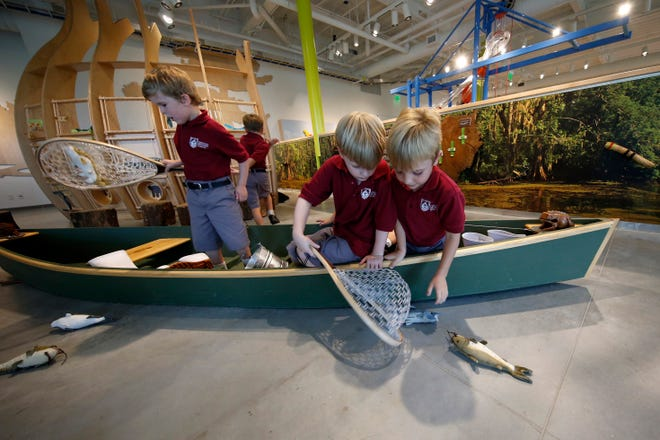 Children from Christian Brothers School try to catch toy catfish with nets while in a pirogue during a preview of the Louisiana Children's Museum on Aug. 27, 2019, at its new location in City Park in New Orleans.