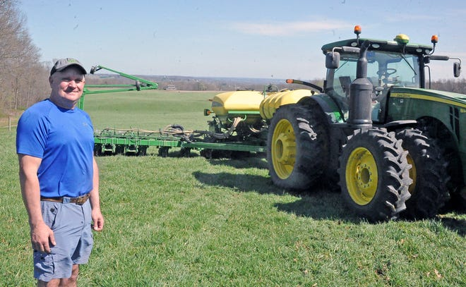 Bruce Tate by his 16-row high-speed corn planter. On a good day, he can plant over 400 acres.