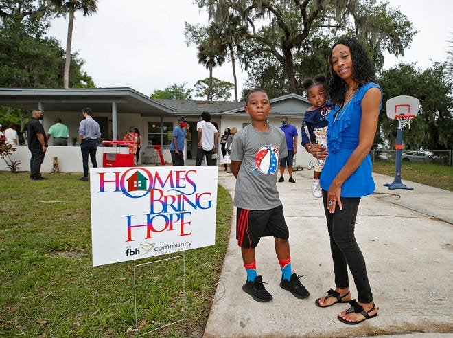 Petra Smiley became the first person to purchase a home through the new Homes Bring Hope program. She and Mendez now live on the same cul-de-sac. Smiley is pictured in April with her children, Miracle and Cairon, at the dedication of their new home in Daytona Beach.