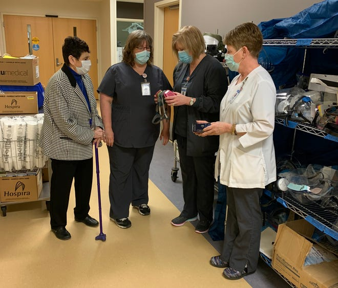 Ellen Eiss, Corry Memorial Hospital emergency department nurse manager, second from right, shows hospital CEO Barbara Nichols, Beth Rouguex, acute care nurse manager, and Patty White, CMH director of patient care services, how to use N95 masks.