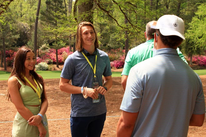Former Clemson quarterback Trevor Lawrence and his fiance Marissa Mowry, left, talk to Patrick Mahomes of the Kansas City Chiefsa as they watch play on the 13th hole during the first round of the Masters at Augusta National Golf Club on Thursday, April 8, 2021, in Augusta, Georgia. (Mike Ehrmann/Getty Images/TNS)