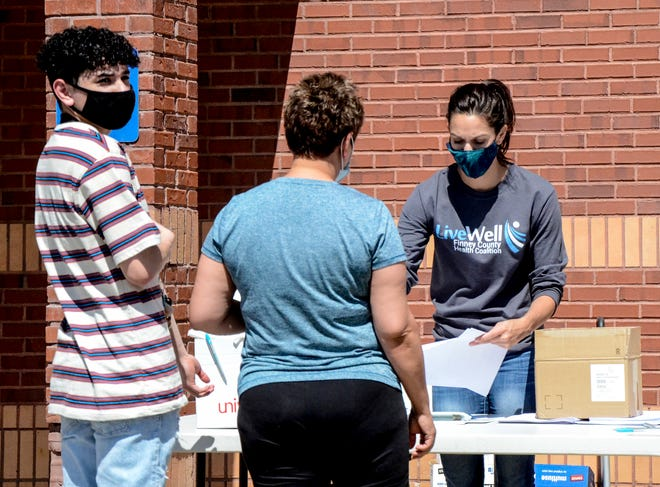 Brigett Clark, right, helps a pair of local residents with the paperwork involved in getting the COVID-19 vaccine Thursday at East Garden Village during a mobile vaccination/testing clinic.