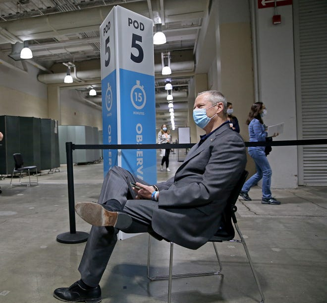 He needs to wait 15 minutes, just like everybody else. Gov. Charlie Baker sits in the observation area after receiving his first dose of Pfizer's COVID-19 vaccine at the Hynes Convention Center in Boston on Tuesday.