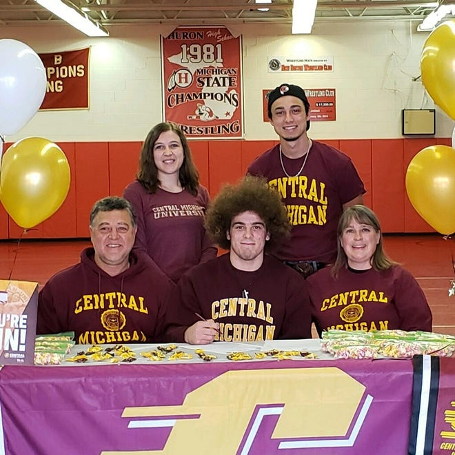 New Boston Huron's Cody Brenner (center) is surrounded by his parents, bother and sister as he signs a scholarship with Central Michigan's wrestling team.