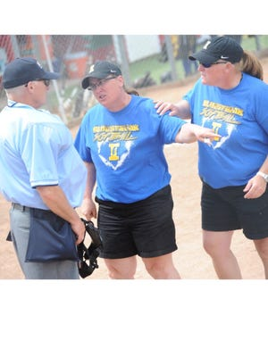 Ida softball coaches Cheryl Hoffman (left) and Dawn Forter (right) dispute a call with an umpire. The two former rivals wound up coaching together for 17 years.