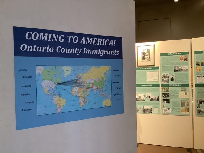 """""""Coming to America"""" is written in many different languages on either side of the world map showing the national origins of immigrants to Ontario County."""