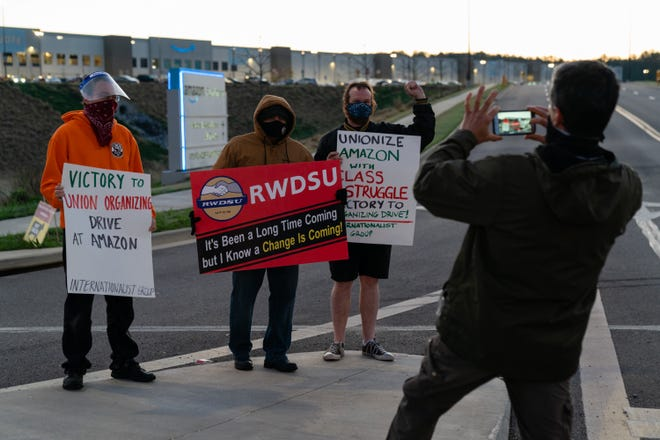 A supporter of the RWDSU unionization effort takes a photo of the RWDSU union rep standing with other supporters outside the Amazon fulfillment warehouse at the center of a unionization drive on in Alabama.