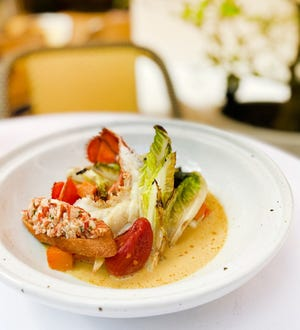 Le Bilboquet's lobster curry features lobster tail baked in the shell and claw meat served tartare style on a crouton.
