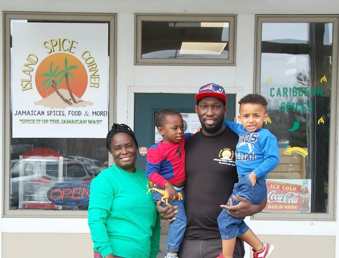 Avenique White and Oneil Clarke with their sons, Malique, 2, and Cole, 4, stand in front of their Island Spice Corner store in York, Maine.