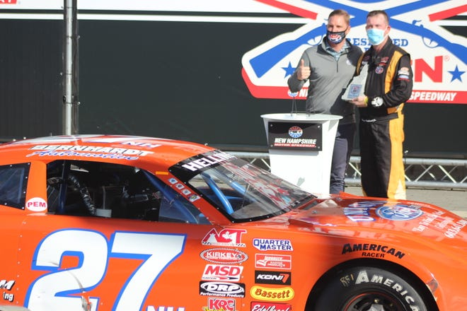 Dover's Wayne Helliwell is presented with the trophy for winning last year's American Canadian Tour event at New Hampshire Motor Speedway.