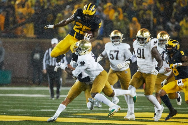 Oct 26, 2019; Ann Arbor, MI, USA; Michigan Wolverines running back Hassan Haskins (25) leaps over Notre Dame Fighting Irish linebacker Jeremiah Owusu-Koramoah (6) in the first half at Michigan Stadium. Mandatory Credit: Rick Osentoski-USA TODAY Sports