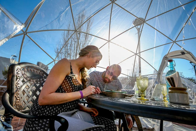 Diners James Messina and Katherine Gobell order during their 5pm reservation in one of the Dining Igloos outside Chaska at Garden City.
