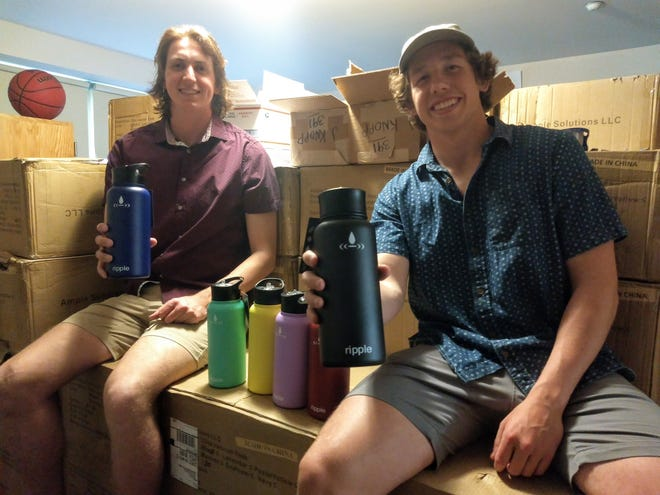 Chip Gottschalk (left) and Joe Knopp display some Ripple water bottles contained from one of the boxes jammed in their Walsh University dorm room. Money raised from the sale of the bottles will be used to construct a water well in an a community in Africa.