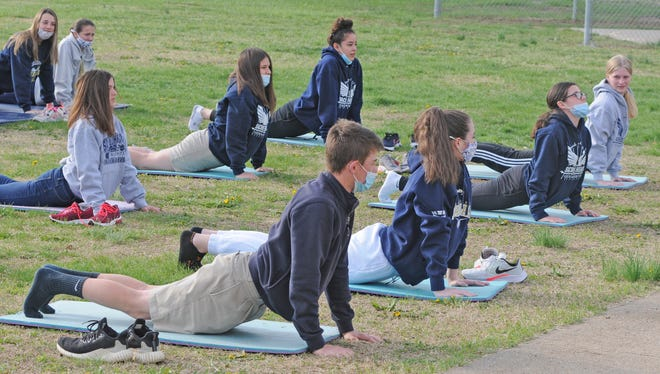 Sacred Heart students stretch while doing yoga outside of the school with class being taught by Angel Wolf, Sharp Performance trainer, during the school health fair on Friday.