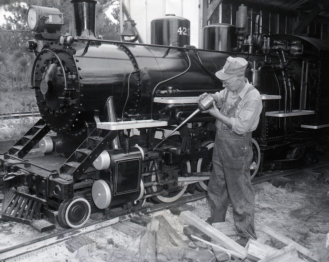 Fred Perry oils the steam locomotive he and his brother built in the backyard of his home on South Whitney St. in St. Augustine in this photograph from the 1960s.
