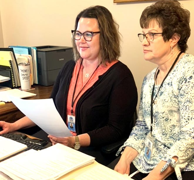 Pat Kulikowski, right, reviews work details with her successor, Jessica Miller. Kulikowski has worked for 34 years as a county employee, working as administrative assistant to three administrators.