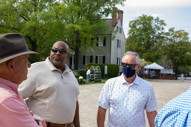 Lieutenant Governor Mark Robinson, second from left, and State Representative Steve Tyson talk with Tryon Palace Foundation member Randy Hunter on the Tryon Palace grounds.
