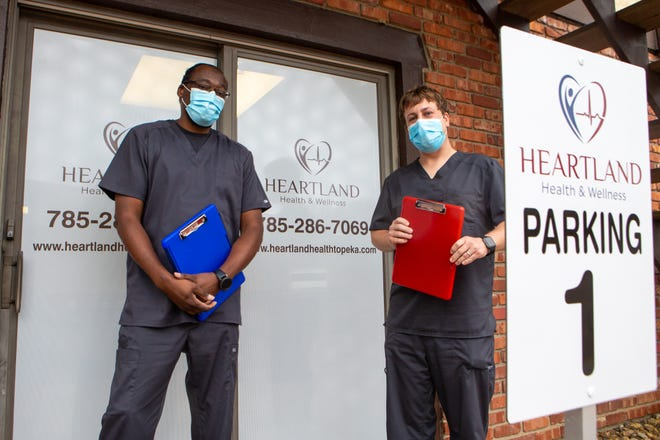 Heartland Health & Wellness owners Kenneth Troupe Jr., left, and Matthew O'Shea stand outside their new clinic Wednesday. The clinic, 5865 S.W. 29th St., opened early with limited hours, so Troupe and O'Shea could offer drive-up COVID-19 tests.