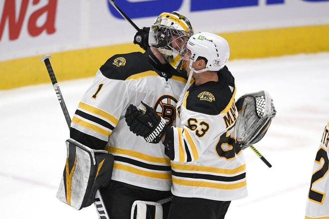 Bruins goaltender Jeremy Swayman and left wing Brad Marchand celebrate after defeating the Washington Capitals on Thursday in Washington. The Bruins won 4-2.
