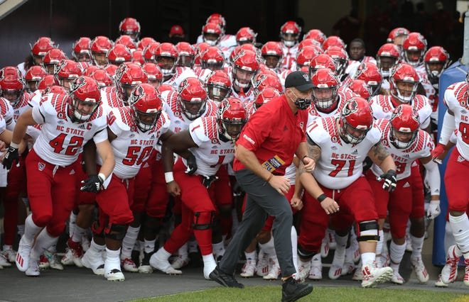 Oct 3, 2020; Pittsburgh, Pennsylvania, USA;  North Carolina State Wolfpack head coach Dave Doeren (middle) leads the team onto the field to play the Pittsburgh Panthers at Heinz Field.