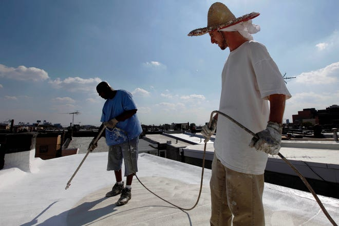 Workers apply a white coating to the roof of a row home in Philadelphia. Painting roofs white could help address global warming.