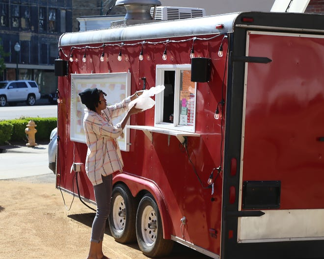 Monique Wilkins picks up an order, Thursday, April 8, at the World of Fries food truck, 913 Garrison Ave., in the Garrison Commons pocket park in Fort Smith.
