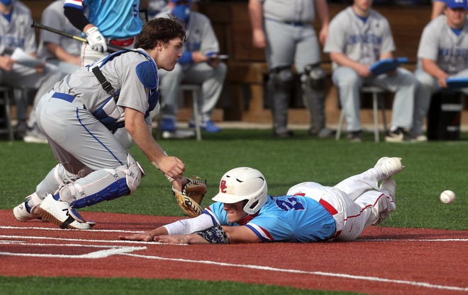 Grove City's Tyler Biddle beats the throw home, sliding safely past Hilliard Davidson's Blake Pettit during a home game March 30. The installation of turf, including on the basepaths, means you won't see a quintessential baseball scene of dirt getting kicked up during a play at the plate.