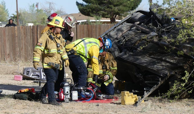 Apple Valley Fire Protection District and San Bernardino County Fire personnel attend to the trapped driver of an overturned Honda Accord in the front yard of an Apple Valley home on Thursday April 8, 2021. The driver, who allegedly fled from a deputy before the crash, died at the scene.
