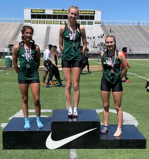 Waxahachie Lady Indians Emma Curry (center), Emilee Jones (left) and Alyson Moore stand on the medal podium after the trio swept the top three finishes in the 3,200-meter run on Wednesday at the District 11-6A meet in DeSoto.