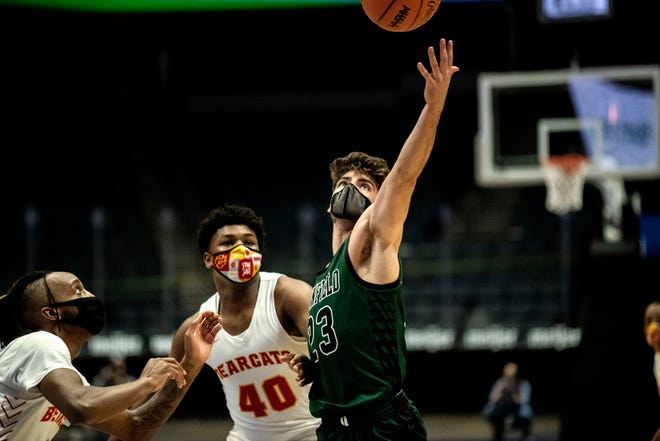 Pennfield senior Ryne Petersen (23) controls the ball as Bridgeport sophomore Zalyn Martin (40) guards him on Thursday, April 8, 2021 at Van Andel Arena in Grand Rapids, Mich. Pennfield defeated Bridgeport 62-52 in the Division 2 State Semifinal contest.