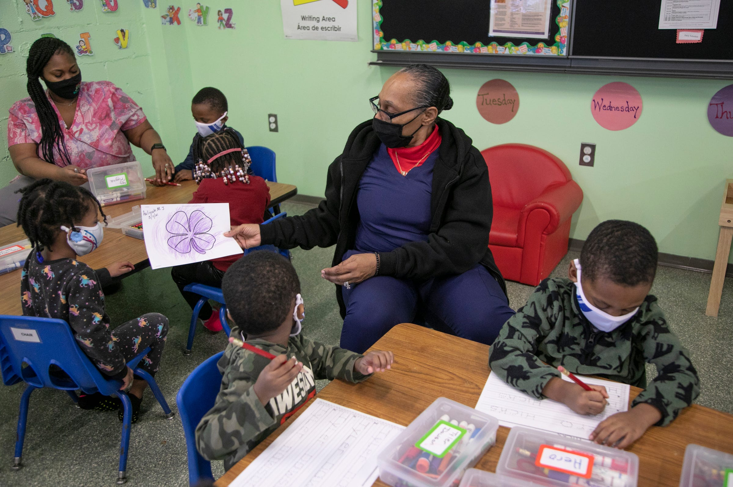 Lead teacher Regina Bride, middle, looks at a student's work on Mar. 11, 2021 as she teaches at the Franklin Wright Settlements in Detroit that turns 140 this year. The organization is all about helping Detroiters with basic life, social and family needs.