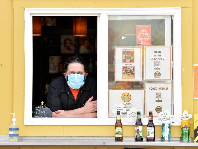 Pemilik Mudgie Deli dan Wine Shop, Greg Mudge, dari Ferndale, berpose di jendela bagasi, Jumat, 9 April 2021.