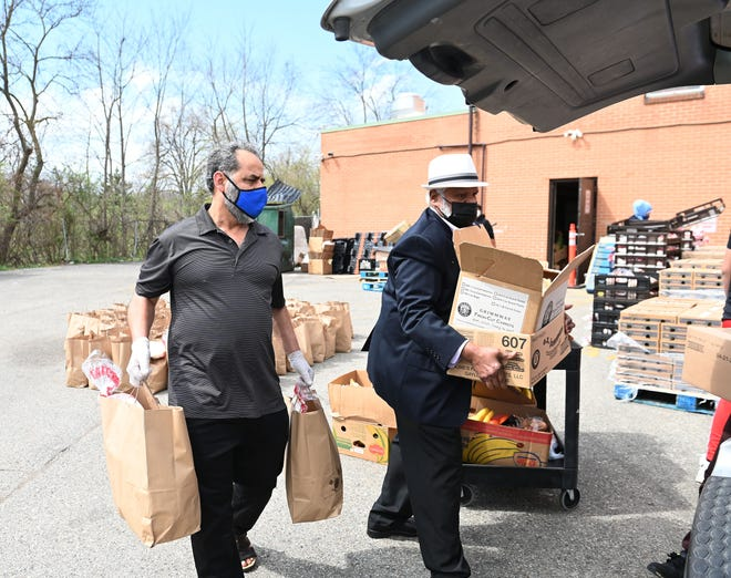 Younis Alseimari, left, and Fareed Baksh load a vehicle with food.