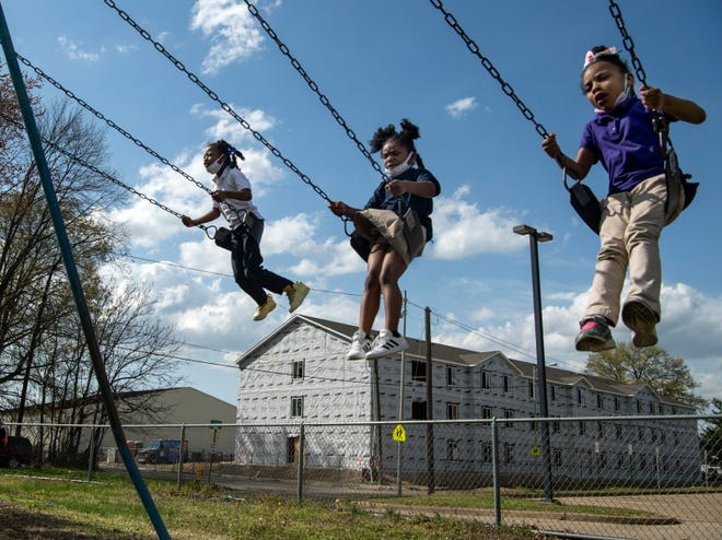 Cashmeir Steverson, from left, Kyndreed Barber and A'riyah Adviento work hard to see how high they can swing during the after school program held at Lincoln School in Evansville, Ind., Wednesday afternoon, April 7, 2021. A new housing development called Memorial Lofts, pictured, is being built across the street from the school, which will feature 26 units of one, two and three-bedroom apartments.