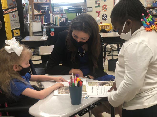 Tennessee Department of Education Commissioner Penny Schwinn follows along as Denmark Elementary first graders Anisia Barzano and Xhy'lah Bufford do peer reading on Thursday, April 8, 2021.