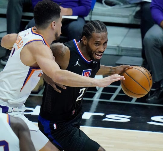 Apr 8, 2021; Los Angeles, California, USA; LA Clippers forward Kawhi Leonard (2) moves to the basket defend by Phoenix Suns guard Devin Booker (1) during the first quarter at Staples Center. Mandatory Credit: Robert Hanashiro-USA TODAY Sports