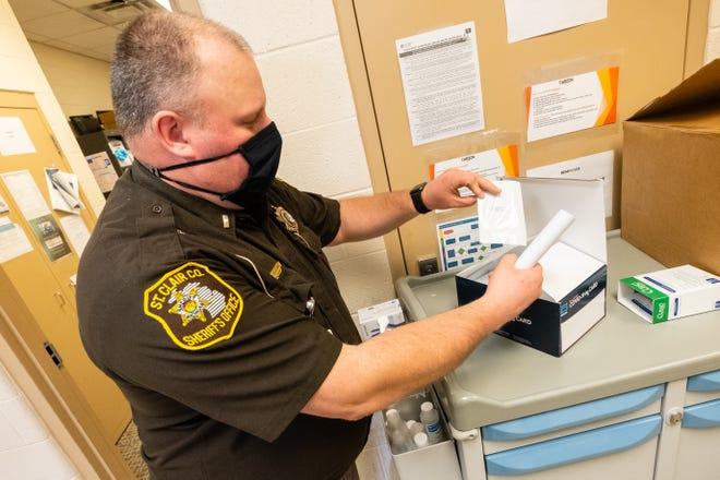 St. Clair County Sheriffs Lt. Richard Olejnik unboxes a COVID-19 rapid test kit Thursday, April 8, 2021, at the St. Clair County jail.