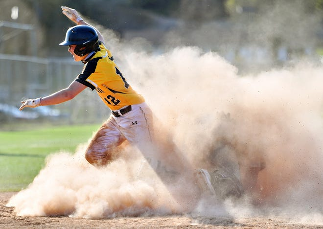Red Lion's Christian Dennison emerges from a cloud of dirt after sliding safely into home plate during baseball action at Red Lion Area Senior High School in Red Lion, Thursday, April, 8, 2021. Red Lion would win the game 4-2. Dawn J. Sagert photo