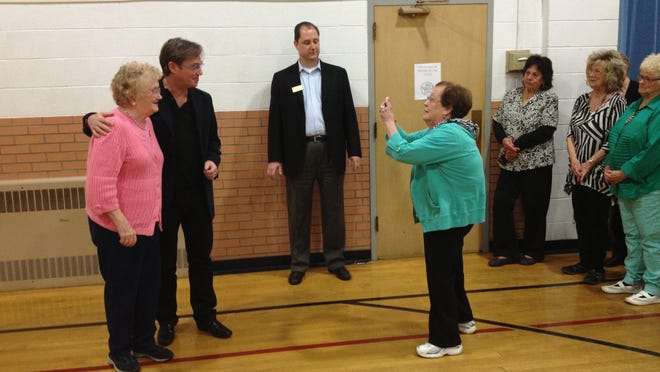 Jane Myers takes a photo of her friend Wanda Logan with actor Richard Thomas in April 2013.  Ambassador Healthcare co-owner Tim Sadler stands between Myers and Thomas.