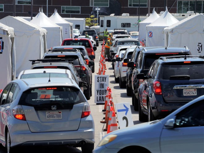 Motorists sit inside their vehicles as they wait their turn to be inoculated with a COVID-19 vaccine at the California State University, Los Angeles campus in Los Angeles, Thursday, April 8, 2021.