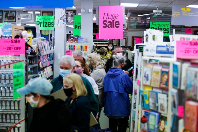 Shoppers wait in line to checkout as they pack National Art Shop on Thursday, April 8, 2021 during a closing sale. The owners are retiring after more than 50 years in business.