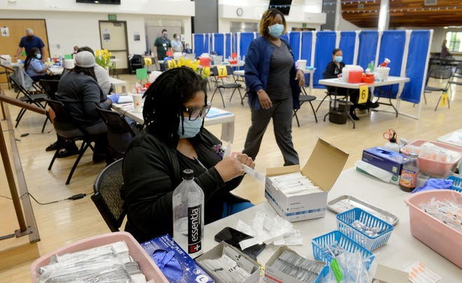 Health-care worker Felicia Grant prepares syringes for Pfizer COVID-19 vaccine at the Goebel Adult Community Center in Thousand Oaks on Thursday, April 8, 2021.