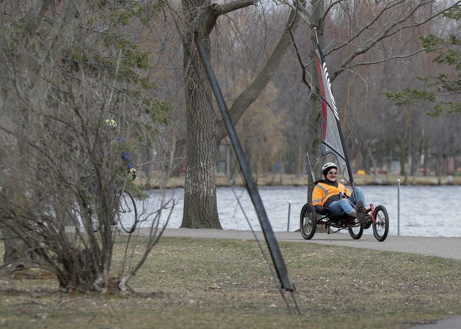 Axel Schmetzke rides his recumbent sail tricycle along the Wisconsin River in Stevens Point. The tricycle uses a sail to assist the rider, allowing the rider to reach high speeds and cover more distance.