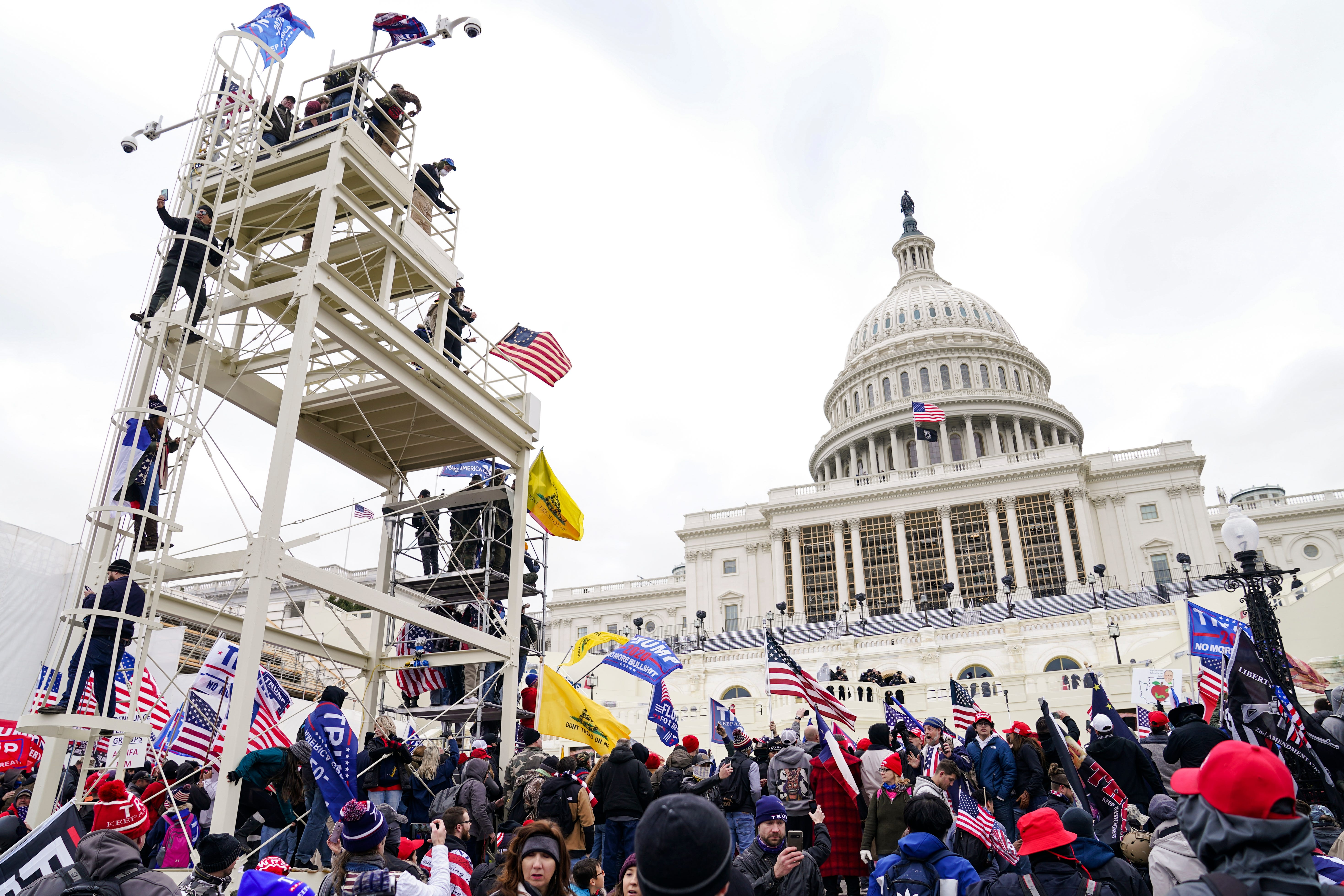 Supporters loyal to President Donald Trump clash with authorities before successfully breaching the Capitol building during a riot on the grounds, Wednesday, Jan. 6, 2021. A number of lawmakers and then the mob of protesters tried to overturn America's presidential election, undercutting the nation's democracy by attempting to keep Democrat Joe Biden from replacing Trump in the White House.