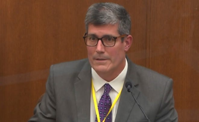 In this image from video, Dr. Andrew Baker, Hennepin County Medical Examiner, testifies as Hennepin County Judge Peter Cahill presides Friday, April 9, 2021.