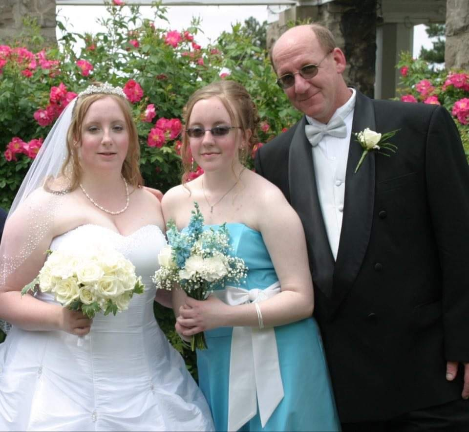 Melissa Burgess, in the middle, with her sister and father.