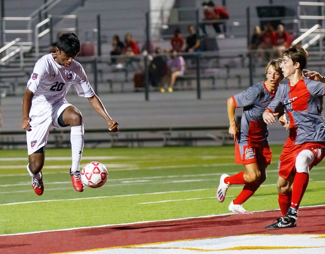 Lake Travis Cavaliers' Ben Paranidharan, left, tries to fire off a shot just before the end of the first half against the San Antonio LEE  Volunteers at the Class 6A Region IV final boys soccer playoff game on Friday at Dripping Springs High School.