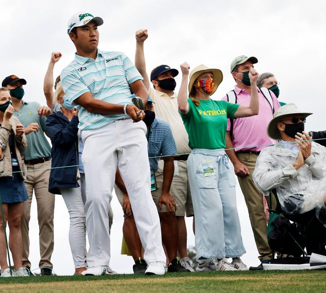 Patrons cheer as Hideki Matsuyama almost chips in on No. 18 to save par and his four stroke lead.