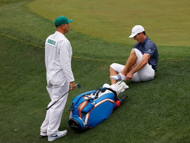 Billy Horschel puts on his shoes and socks after hitting out of Rae's Creek on no. 13 during Saturday's third round for the Masters at Augusta National Golf Club, Saturday, April 10, 2021, in Augusta, Georgia.