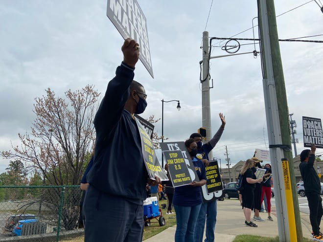 Protesters gather at the intersection of Berckmans and Washington roads to speak out against Georgia Senate Bill 202 on Saturday.